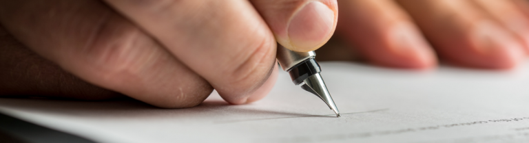 Close up of hand holding ink pen signing a document