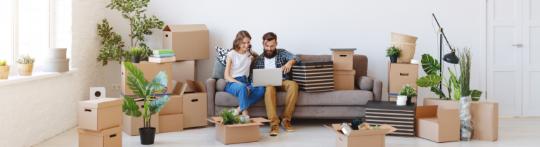 Couple sitting among packing cases and boxes