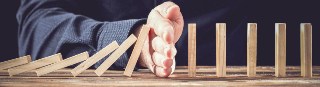 Hand preventing dominoes tumbling